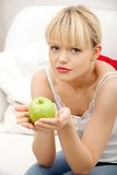 Beautiful woman on couch holding an apple. Royalty Free Stock Image