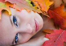 Beautiful woman covered in leaves. Close up portrait of a beautiful woman covered with colorful leaves Royalty Free Stock Photos