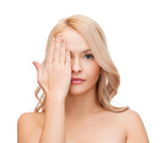 Beautiful woman covering half of face with hand Stock Images