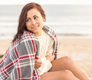 Beautiful woman covering herself with blanket at beach Royalty Free Stock Image