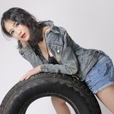 A wild and beauty. The beautiful woman in the cowboy jacket was in good shape on the tire. She`s and wild stock image