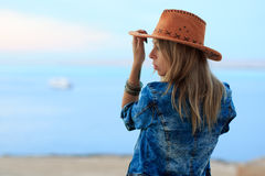 Beautiful woman in cowboy wild west style, cowboy hat and jeans jacket, fashion portrait photosession, advertising, sea view lands Royalty Free Stock Images