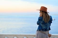 Beautiful woman in cowboy wild west style. Cowboy hat and jeans jacket, fashion portrait photosession, advertising, sea view landscape, blue sky sunset stock images