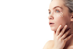 Beautiful woman with cream drops on face on white background Royalty Free Stock Image