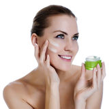Beautiful woman with cream on the face Stock Images