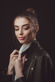 Beautiful woman with creative hairstyle in leather jacket. Studio shoot of beautiful woman with bright makeup and creative hairstyle in leather jacket Stock Photo