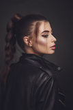 Beautiful woman with creative hairstyle in leather jacket. Studio shoot of beautiful woman with bright makeup and creative hairstyle in leather jacket Royalty Free Stock Image