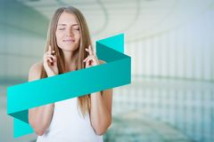 Beautiful woman with crossed fingers and banner. Portrait of beautiful young woman with crossed fingers and empty web banner standing on blurry interor Stock Photos