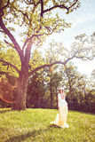 Beautiful woman with a crown of chamomiles on her head in the park Stock Images