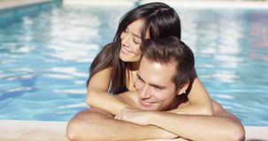 Beautiful woman cuddles with her boyfriend in pool stock video footage