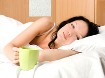 Beautiful woman with a cup of coffee in bed Royalty Free Stock Photo