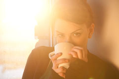 Beautiful woman with cup of coffee over sun window. Beautiful young woman in casual wear dreaming with cup of hot coffee over window. Sun beam Royalty Free Stock Photography