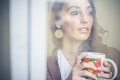 Beautiful woman with cup facing through window Royalty Free Stock Images