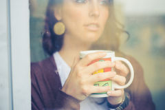 Beautiful woman with cup facing through window Stock Images