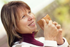 Beautiful woman with a cup in hands on the street Stock Images