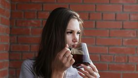 Beautiful woman with a cup of hot tea. A girl drinks tea on a brick wall background stock video
