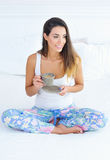 Beautiful woman with a cup of morning coffee in bed Stock Image