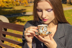 Beautiful woman with a Cup of tea in the beautiful makeup sitting in the Park on a bench and drink hot tea in the autumn Sunny day Stock Photos