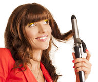 Beautiful woman curling her brunette hair Royalty Free Stock Images