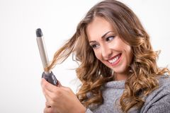 Beautiful woman with curling iron royalty free stock photos