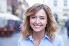 Beautiful woman with curly blond hair in the city Royalty Free Stock Photo
