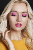 Beautiful woman with curly blond hair and evening make-up. Jewelry and Beauty. Fashion art photo. Pink make-up Royalty Free Stock Image
