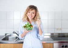 Beautiful woman with curly blond hair with salad in the kitchen Stock Photography