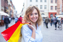 Beautiful woman with curly blond hair and shopping bags in the city Stock Photography