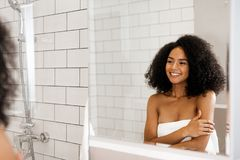 Beautiful woman with curly hair. Looking at her reflection in bathroom Royalty Free Stock Photos