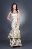 Beautiful woman with curly hair in golden dress Royalty Free Stock Photos