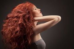 Beautiful woman with curly hair on gray background Stock Images