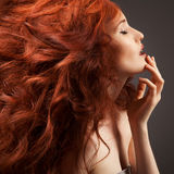 Beautiful woman with curly hair on gray background Royalty Free Stock Images