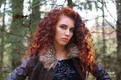 Beautiful woman with curly hair in leather jacket. In sunny autumn forest, shallow dof Stock Image