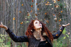 Beautiful woman with curly hair in leather jacket. Throws up dry leaves in sunny autumn forest Royalty Free Stock Photography