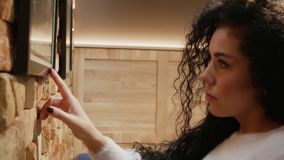 Beautiful woman with curly hair looks at the picture on the wall stock footage