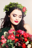 Beautiful Woman with Curly Hair, Makeup and Flowers Royalty Free Stock Photography