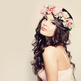 Beautiful Woman with Curly Hair, Makeup and Flowers Stock Photography