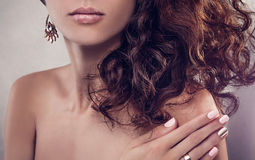 Beautiful woman with curly hair and manicure. On grey background Royalty Free Stock Photo