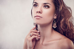 Beautiful woman with curly hair and manicure. On grey background Royalty Free Stock Photography