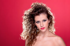 Beautiful woman with curly hair on red Royalty Free Stock Images
