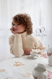Beautiful woman with curly hair sitting at table, in warm sweater, drink coffee at outdoor Stock Photo