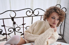 Beautiful woman with curly hair sitting at table, in warm sweater and white stockings, relaxing at outdoor Royalty Free Stock Images