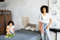 A beautiful woman with curly hair is standing in the room by the bed, and her daughter is sitting on the bed and holding a tulip. A beautiful women with curly stock images