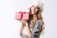 Beautiful woman with curly hair wearing a hat and sweater holding a pink box with a gift. Royalty Free Stock Image