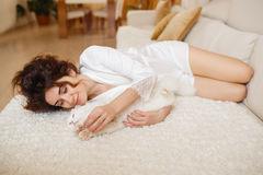 Beautiful woman with curly hair in a white silk dressing gown early in the morning playing with white fluffy cat sitting on sofa Royalty Free Stock Images
