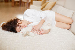 Beautiful woman with curly hair in a white silk dressing gown early in the morning playing with white fluffy cat sitting on sofa Royalty Free Stock Image