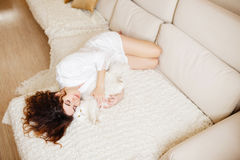 Beautiful woman with curly hair in a white silk dressing gown early in the morning playing with white fluffy cat sitting on sofa Stock Photo