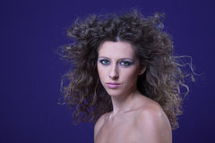 Beautiful woman with curly hair on wind, on purple. Studio shot Stock Photography