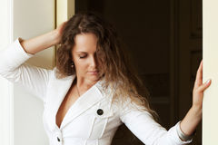 Beautiful woman with curly hairs looking down. Sad beautiful woman with long curly hairs looking down Royalty Free Stock Photos