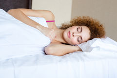 Beautiful woman with curly red hair sleeping in bed Royalty Free Stock Photos